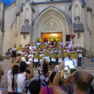Apresentação do coral das crianças do COHCRIC na escadaria da Matriz de São Sebastião.